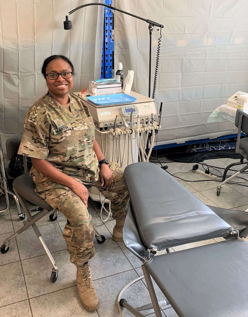 "Kentucky National Guard Maj. Mitisha Martin poses Aug. 20, 2020, in Poland with the 1163rd Area Support Medical Company's motto: ""Whatever it takes."""