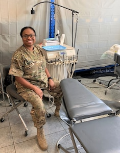 """Kentucky National Guard Maj. Mitisha Martin poses Aug. 20, 2020, in Poland with the 1163rd Area Support Medical Company's motto: """"Whatever it takes."""""""