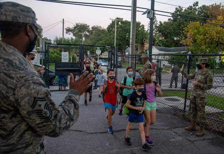 Members of Team MacDill greet students on their way to school at Roosevelt Elementary in Tampa, Fla., Oct. 15, 2020.