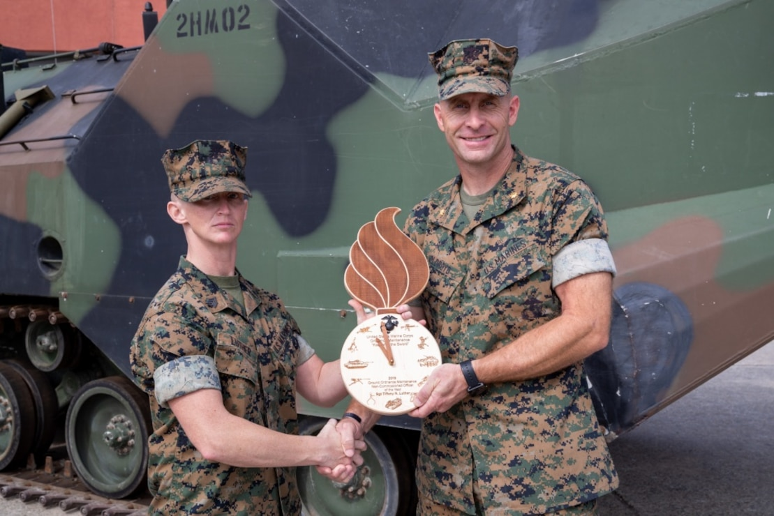 "U.S. Marine Corps Sgt. Tiffany Luther, left, former assistant battalion maintenance chief with 2nd Assault Amphibious Battalion, 2nd Marine Division (2d MARDIV), and Maj. Mark Oldroyd, the 2d MARDIV Ordnance Officer, pose for a picture after Luther received the 2019 Ground Ordnance Maintenance Non-Commissioned Officer of the Year Award on Camp Lejeune, North Carolina, Oct. 9, 2020. Luther, a native of Thomasville, North Carolina, who has won the award twice now said, ""It's about stepping outside your comfort zone and striving to be in positions that are challenging. Chase after the challenge and grow with it."" Luther's unwavering determination, unmatched initiative, and uncommon resourcefulness during the North Atlantic Treaty Organization Exercise Trident Juncture 2018 were instrumental in the battalion's combat readiness throughout the exercise. (U.S. Marine Corps photo by Lance Cpl. Jacqueline Parsons)"