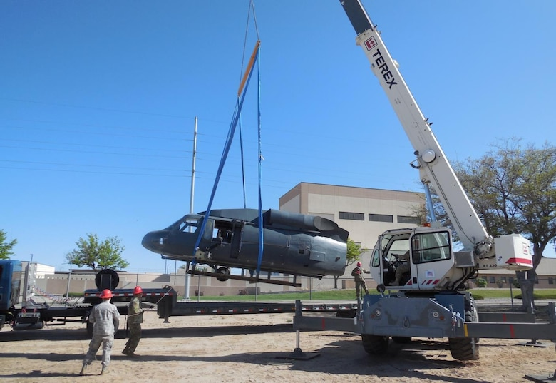 Members of the New Mexico Air National Guard 210th RED HORSE Squadron use a crane and flatbed trailer in April to relocate a modified HH-60 helicopter airframe and training aid from the 58th Training Squadron's aircraft yard to the DNWS training site on Kirtland AFB.