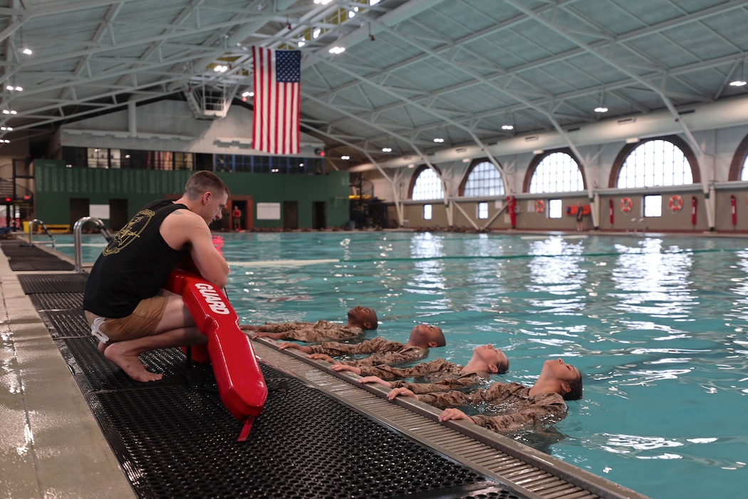 Staff Sgt. Eric. Minton, a Marine Corps Instructor Water Survival, instructs the recruits on one of the swim qualification events at Marine Corps Recruit Depot Parris Island, S.C., Dec. 17, 2019. During the swim qualification course the recruits are required to complete a series of basic water survival techniques to continue on with training. (U.S. Marine Corps photo by Lance Cpl. Samuel C. Fletcher)