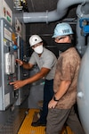 Environmental Zone Manager Patrick Williams (Code 990E) and Industrial Equipment Work Leader Ricky McCadden (Code 990E) working together in the new tank space.