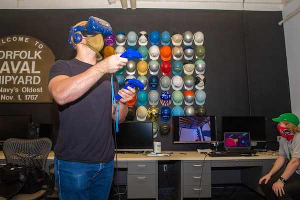 NNSY Photographer Danny DeAngelis test drives the virtual reality simulation in the NNSY Technology and Innovation Lab while Assistant Shift Test Engineer Joey Hoellerich stands by to assist.