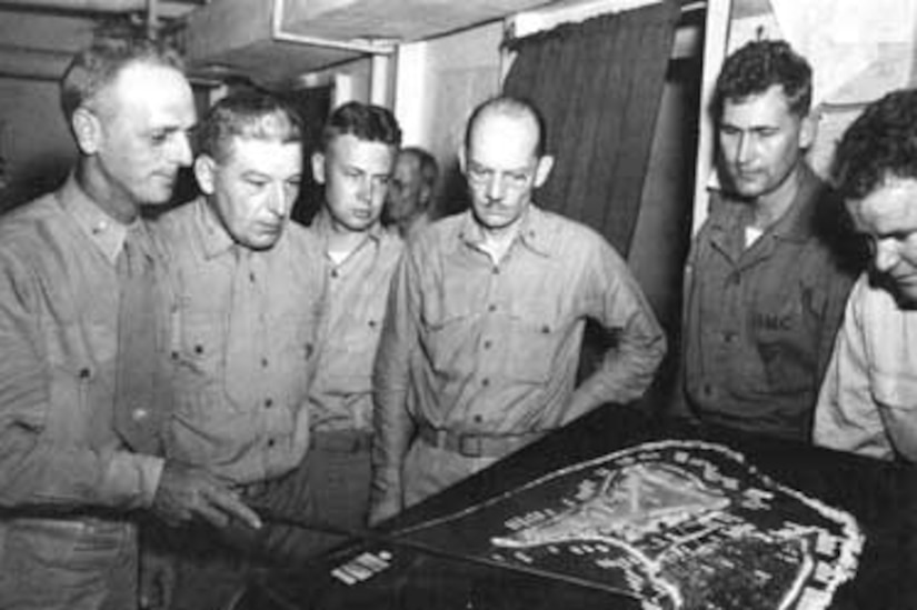 A Marine officer briefs others using a large, table-top map.