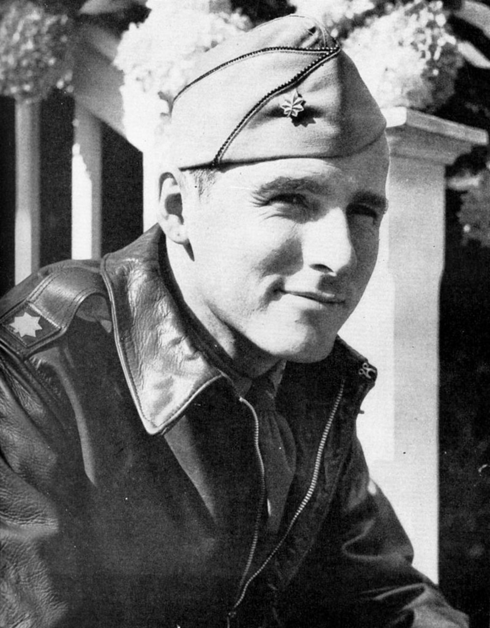 A man in World War II army uniform poses for a photo.