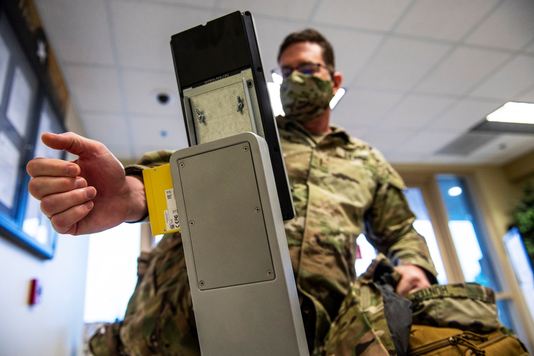 A soldier wearing a face mask uses a terminal that screens your temperature.