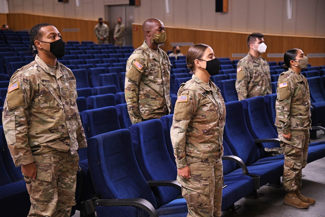 Several male and female soldiers wearing face masks stand at attention during a class graduation.
