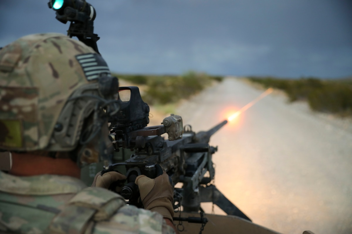 A soldier fires a weapon in a desert-like area.