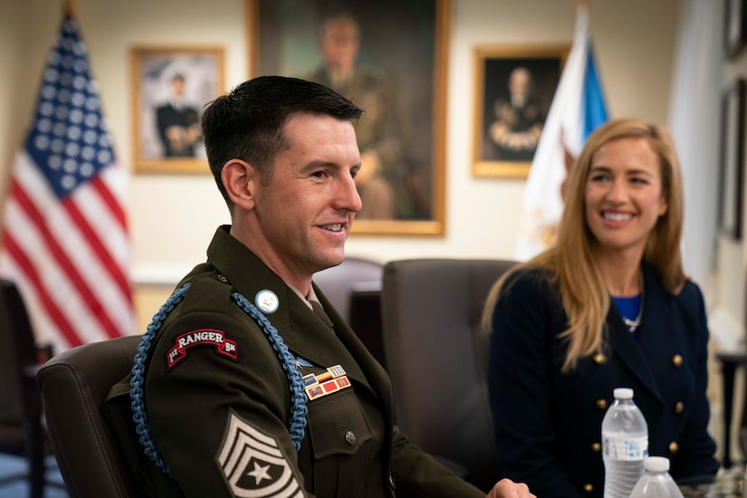 A man and woman, both smiling, sit in chairs in an office. An American flag is in the background.