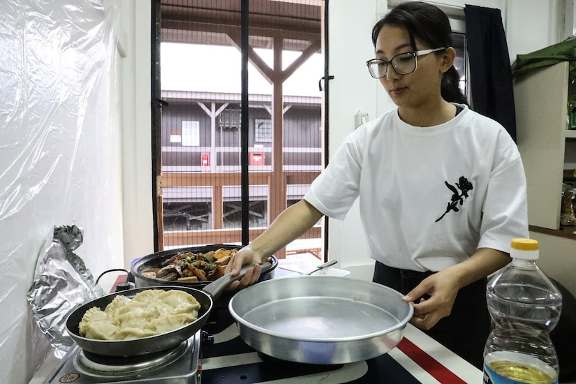 A woman stands over three pans cooking food on the stove.