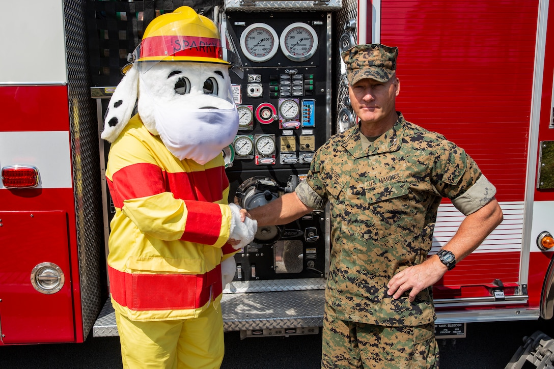 """U.S. Marine Corps Maj. Gen. Julian D. Alford, commanding general, Marine Corps Installations East-Marine Corps Base Camp Lejeune, shakes hands with Sparky the fire dog on MCB Camp Lejeune, North Carolina, Oct. 6, 2020. This year's fire prevention week teaches fire safety, precautions, and awareness while highlighting this year's theme, """"Serve Up Fire Safety in the Kitchen"""" running from Oct. 4-10. (U.S. Marine Corps photo by Lance Cpl. Christian Ayers)"""