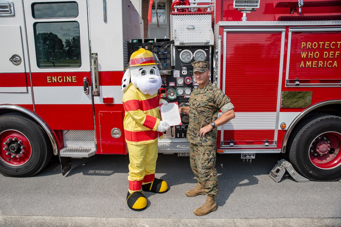 """U.S. Marine Corps Maj. Gen. Julian D. Alford, commanding general, Marine Corps Installations East-Marine Corps Base Camp Lejeune, stands with the fire prevention proclamation with Sparky the fire dog on MCB Camp Lejeune, North Carolina, Oct. 6, 2020. This year's fire prevention week teaches fire safety, precautions, and awareness while highlighting this year's theme, """"Serve Up Fire Safety in the Kitchen"""" running from Oct. 4-10. (U.S. Marine Corps photo by Lance Cpl. Christian Ayers)"""