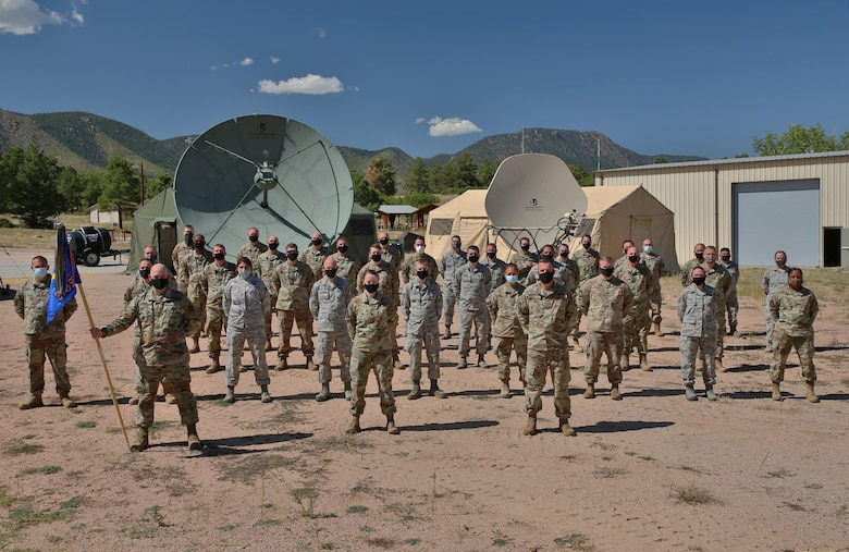 The 379th Space Range Squadron poses in front of their deployable mission equipment during the 379th SRS Field Training Exercise, Sept. 10-13, 2020, at the United States Air Force Academy's Field Engineering Readiness Laboratory, Colorado. Despite obstacles, this event marked the 379th SRS's first major training exercise during the COVID-19 pandemic. (U.S. Air Force photo by Capt. Jordan Wind)