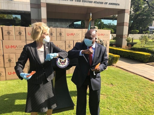 Lana. J.Marks, the United States Ambassador to South Africa, bumps elbows with South African Deputy Health Minister Dr. Joe Phaala