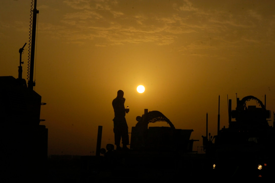 A man and military equipment are in silhouette against an orange, sunset sky.