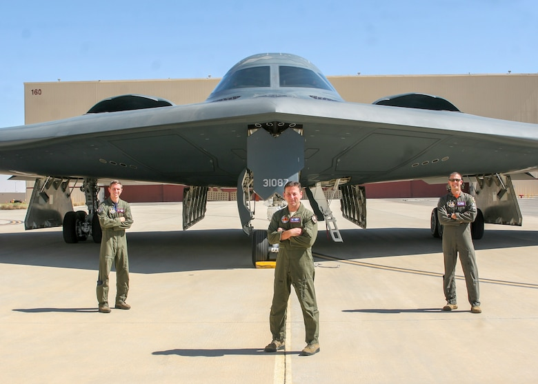 """The 419th Flight Test Squadron's Maj. Matthew Gray, Jason DiGiacomo and Maj. Dustin Duke pose for a photo in front of the B-2 """"Spirit of Pennsylvania"""" after it arrived to Edwards Air Force Base, California, Oct. 2. (Air Force photo by Kyle Brasier)"""