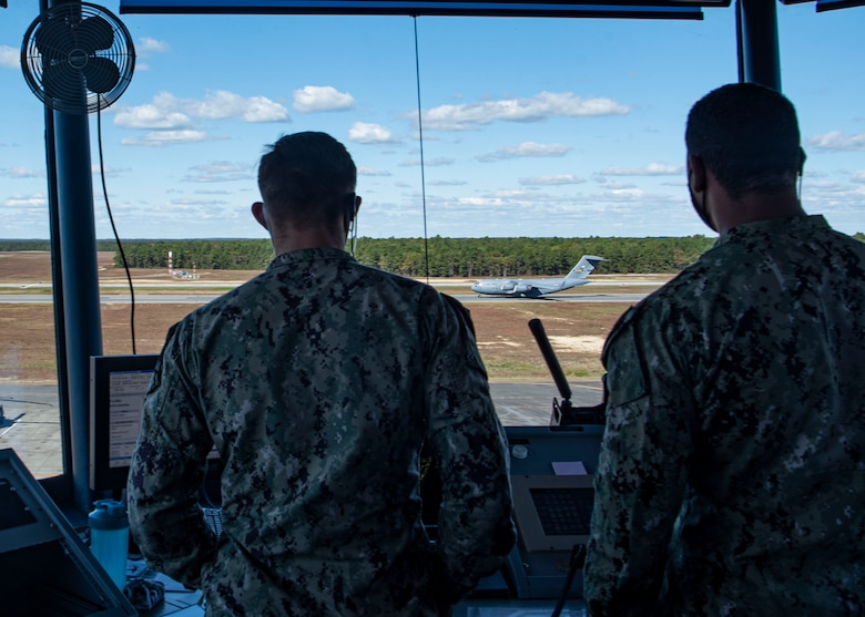 Photo of sailors assigned to the 305th Operations Support Squadron watching a C-17 Globemaster III land.