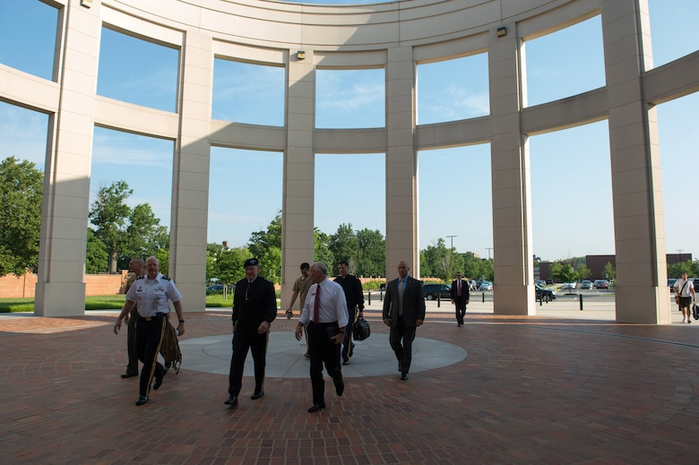 Multiple individuals, some in military uniform, walk outdoors through an array of columns.