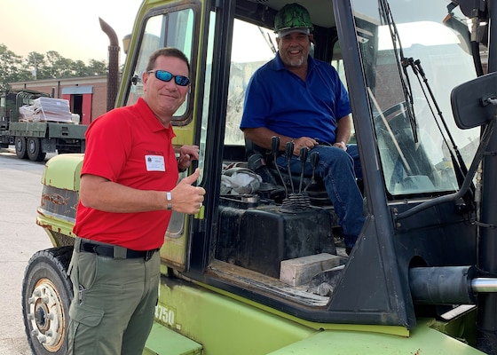 Detective Ben Parrish, Duplin County Sheriff's Department, left, and Darryl Whaley, county garage supervisor, enjoy a moment with the forklift they acquired from DLA Disposition Services at Camp Lejeune, North Carolina.