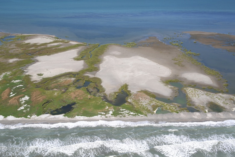 The state of Louisiana constructed two sand berms between 2010 and 2011 to protect the Chandeleur Islands as part of an emergency response plan to mitigate the effects of the Deepwater Horizon oil spill. Most of the sediment placed in the berms mimicked nearshore beneficial use of dredged material applications that are used for barrier island nourishment and restoration. A study found that sediment was transported onto existing island features or across the island into Chandeleur Sound. The build up and reinforcement of the island ensures its viability as wildlife habitat, making this an excellent example of working with natural processes to produce beneficial results. The effort to create the berms and evaluate them was a collaboration between multiple state and federal agencies, including the U.S. Army Corps of Engineers. (U.S. Geological Survey photo by Karen Morgan)