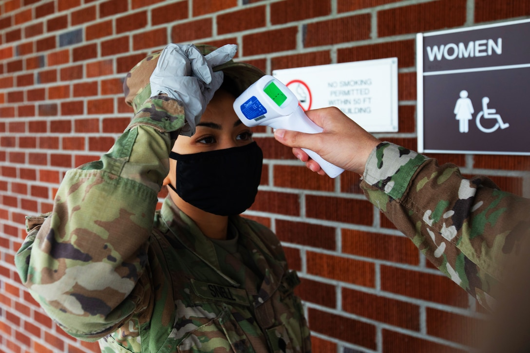 A soldier wearing a face mask lifts her hat for a temperature check.
