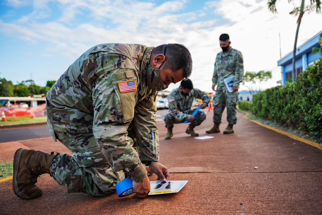 A soldier wearing a face mask kneels to tape down a social distancing sign on the sidewalk.