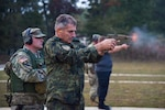 Bulgarian Chief of Defense Adm. Emil Eftimov fires the M-17 handgun, Oct. 8, at a small-arms pop-up range at Volunteer Training Site - Tullahoma.