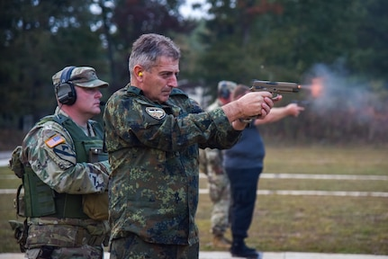 Bulgarian Chief of Defense Adm. Emil Eftimov fires the M-17 handgun, Oct. 8, at a small-arms pop-up range at Volunteer Training Site - Tullahoma. After signing a new training roadmap with the U.S., Bulgarian officials visited the Tennessee National Guard, renewing their partnership through 2030.