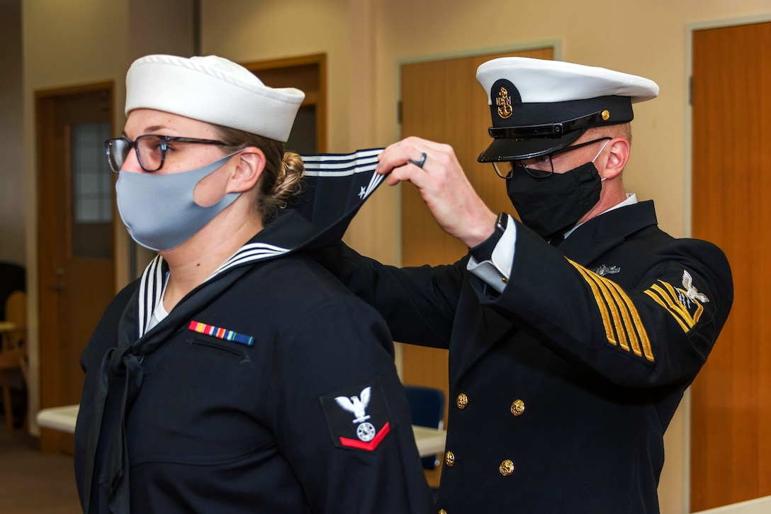 A sailor wearing a face mask inspects another sailor wearing face mask during an inspection.