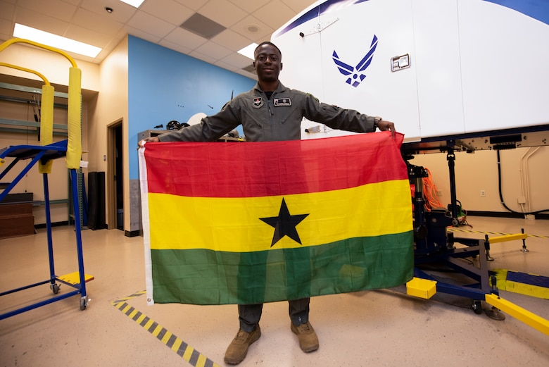 Airman 1st Class Gaddiel Acquaah, a 47th Operations Support Squadron aerospace physiology technician, holds a Ghanaian flag at Laughlin Air Force Base, Texas, Oct. 2, 2020. Acquaah recently received his U.S. citizenship through serving in the U.S. Air Force. Acquaah trains aircrews on everything from handling extreme G-force to egress training. (U.S. Air Force photo by Senior Airman Marco A. Gomez)
