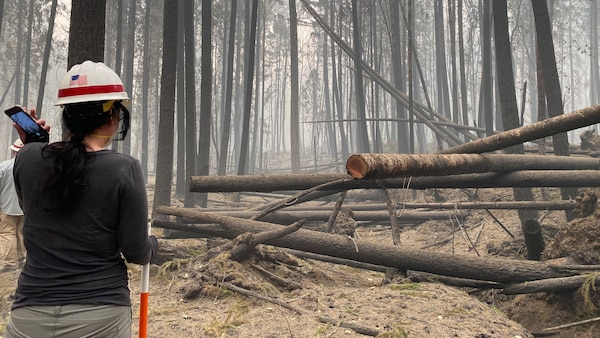 Erica Medley, a dam safety geologist with Portland District, U.S. Army Corps of Engineers, makes her way through thick smoke and fallen trees as she surveys damage on site at Blue River Dam Sept. 14. Medley joined a multi-disciplinary team of operations, engineering and dam safety personnel for a detailed inspection of the project just days after the Holiday Farm Fire burned through the area, impacting Blue River and nearby Cougar Dam.