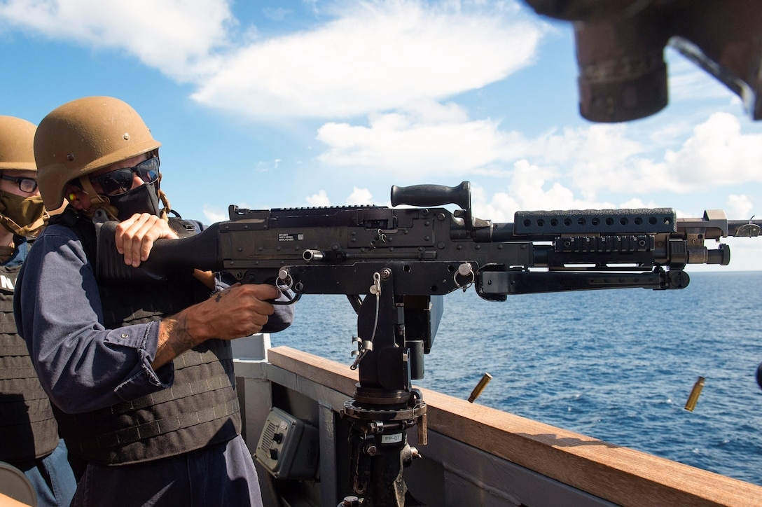 A sailor fires a weapon over the water as another sailor watches.