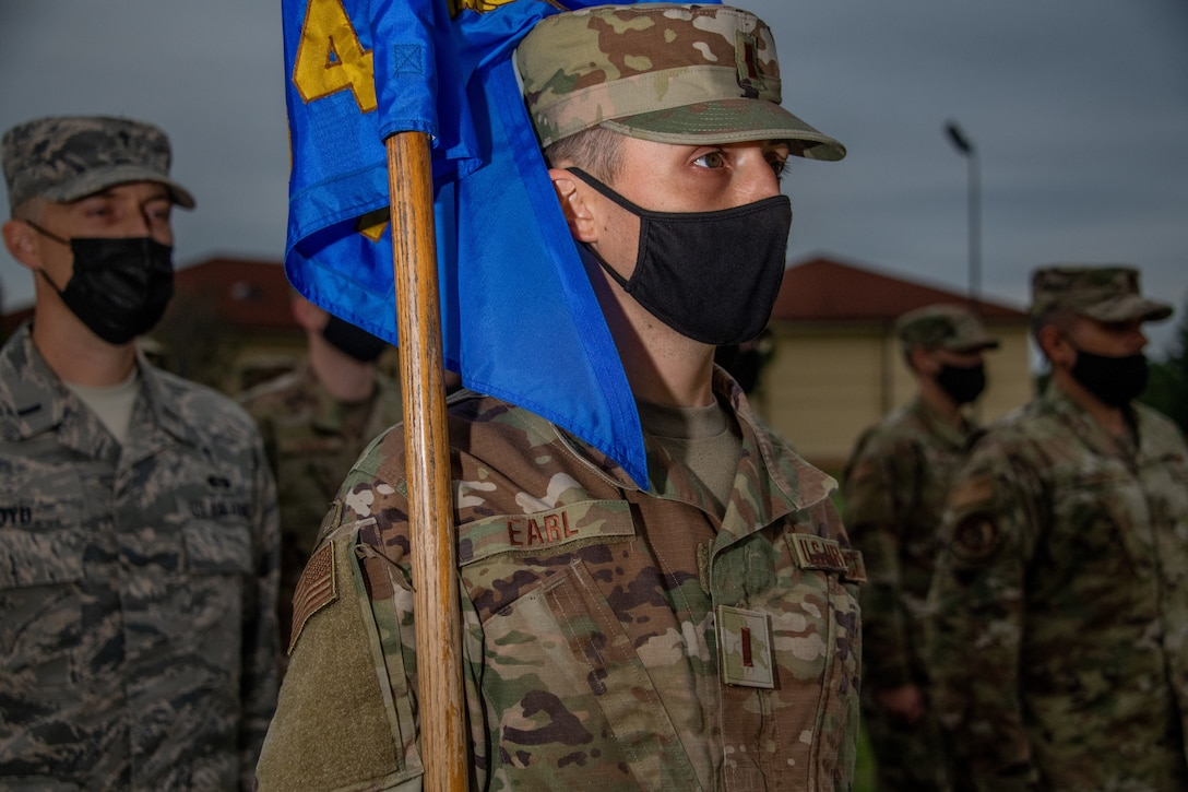 A guidon bearer from Officer Training School Class 20-08 stands at attention during the opening remarks at the OTS parade field