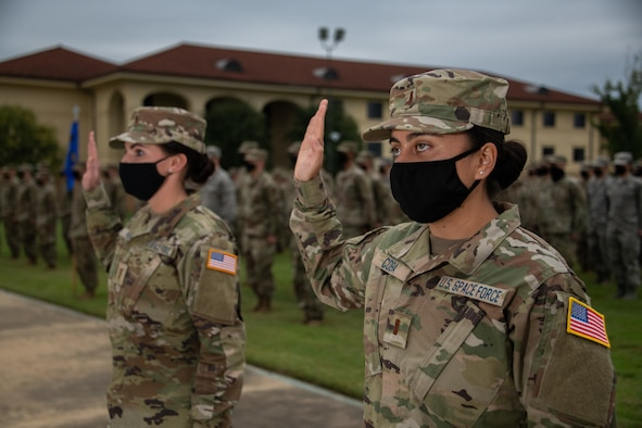 Space Force Second Lieutenants Amy Coba and Elizabeth Kowal, Officer Training School Class 20-08 graduates, raise their right hand and recite the Space Force Oath of Office