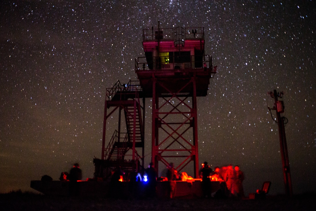 Marines work under a starry sky illuminated by green, red and blue light.