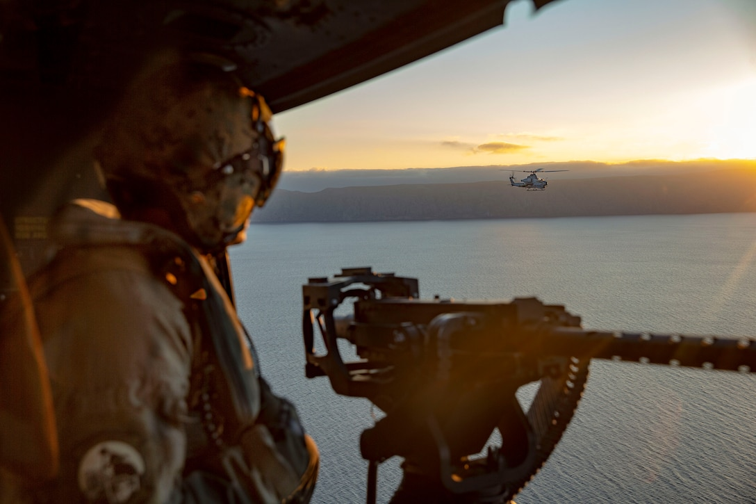 A Marine aboard one helicopter watches another fly over water.
