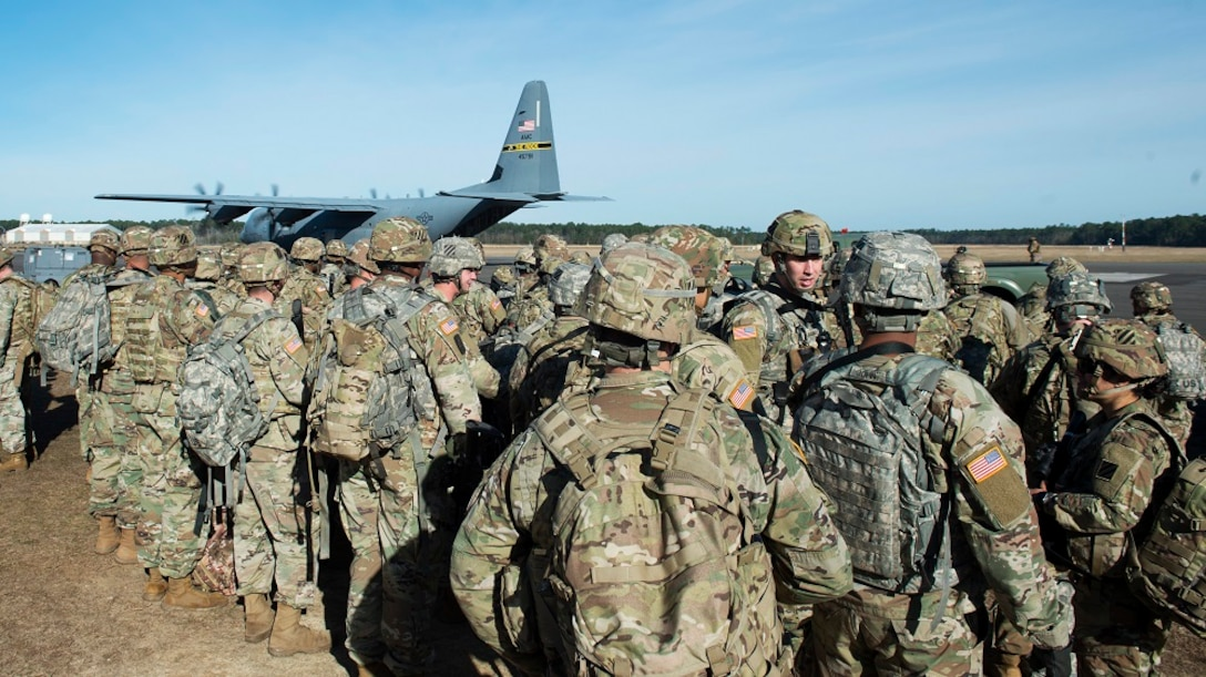 Military members line up for transportation to an exercise location.