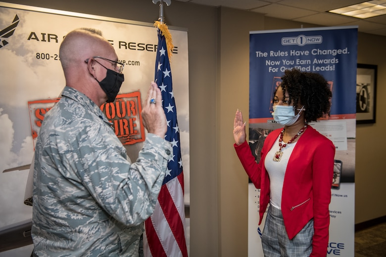 """Dominique Burrell recites the oath of enlistment given to her on Oct. 2 2020 by Lt. Col. Stan Paregien, 932nd Airlift Wing Public Affairs Officer, during an enlistment ceremony at the 932nd AW Headquarters building, Scott Air Force Base, Illinois. Burrell will continue her family's military legacy. """"I will become part of a bigger family,"""" said Burrell """"I hope to someday become an officer and look forward to what the Air Force has to provide [me], such as resiliency.""""  (U.S. Air Force photo by Christopher Parr)"""