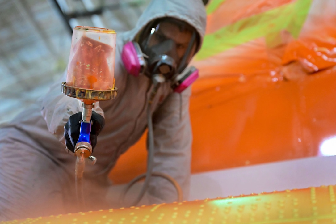 An airman in a protective mask and coveralls spray paints a metal object