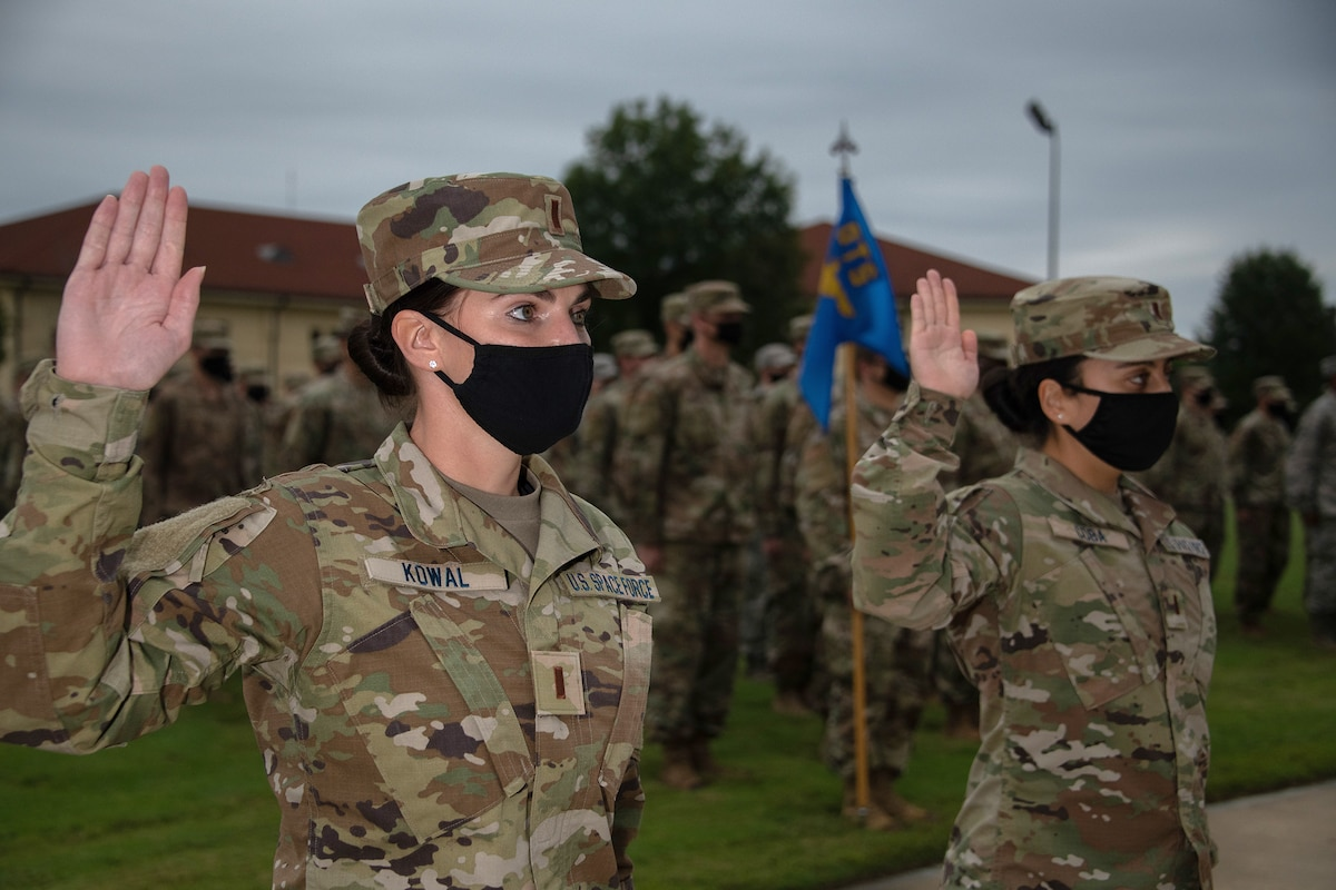 Two Space Force members wearing masks raise their right hands in front of a group of airmen on a parade-type field.