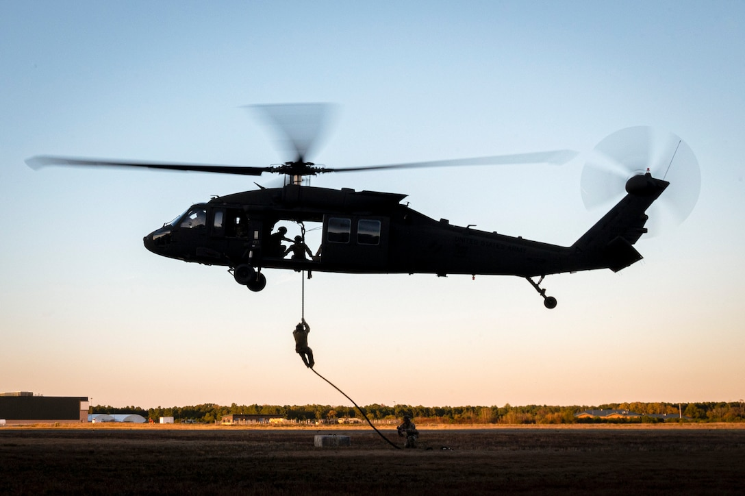An Air National Guardsman fast-ropes from a helicopter in a field-like area as other service members watch.