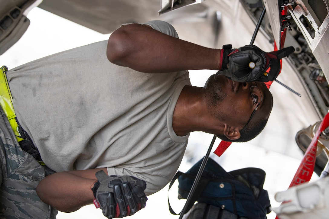 An airman leans to one side and looks up at a section of an aircraft while holding a tool.