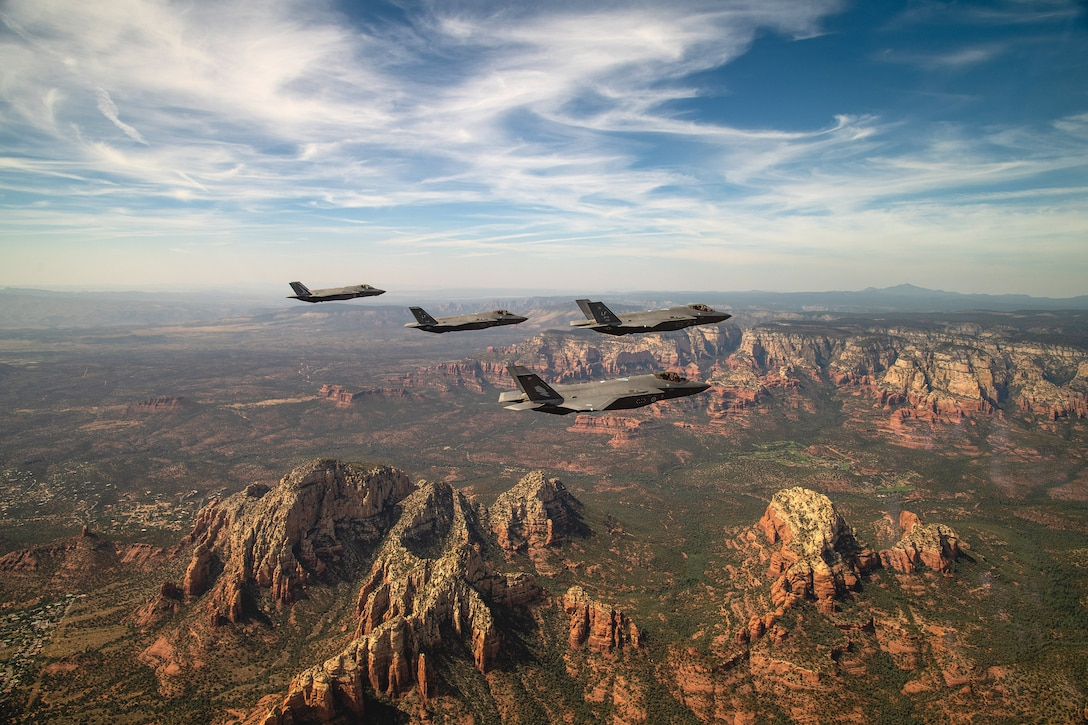 Four aircraft fly in formation over craggy brown mountains.