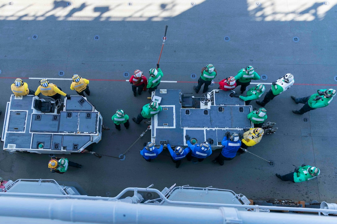 Sailors wearing, seen from above, stand on ship's flight deck, wearing either yellow, red, blue or green shirts.