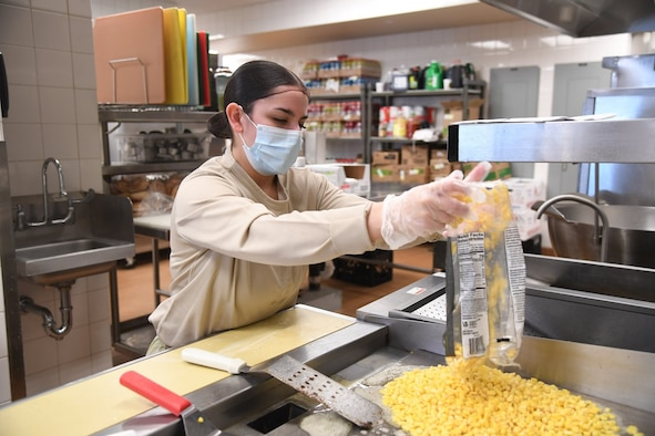 A1C Vanessa Alvarez, food assistant specialist from the 5th Force Support Squadron, is assisting the Prairie Vigilance exercise by working the Alert Diner on the flight line.