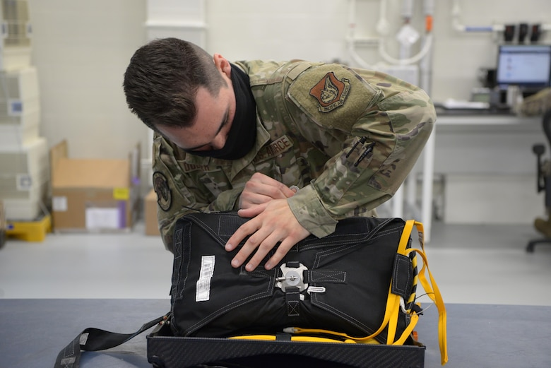 U.S. Air Force Staff Sgt. Ross Dugger, a 354th Operations Support Squadron Aircrew Flight Equipment craftsman, zips up the new arctic survival seat kit for the F-35A Lighting II on Eielson Air Force Base, Alaska, Sept. 25, 2020.