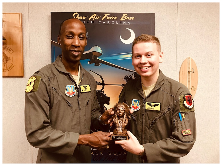 Airman 1st Class Jared, 482nd Attack Squadron, and Lt. Col. Andre, 482nd ATKS, hold a trophy together as they pose for a photo in front of a blue MQ-9 poster.