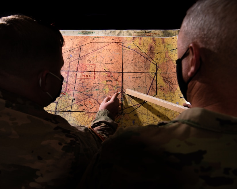 Two service members look at a map.