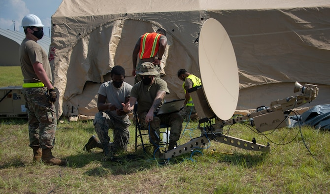 men work on a satellite dish